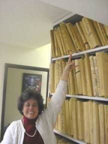 Music Restorer Kathleen Mayne at Warner Brothers Music Library, pointing to scores from THEM
